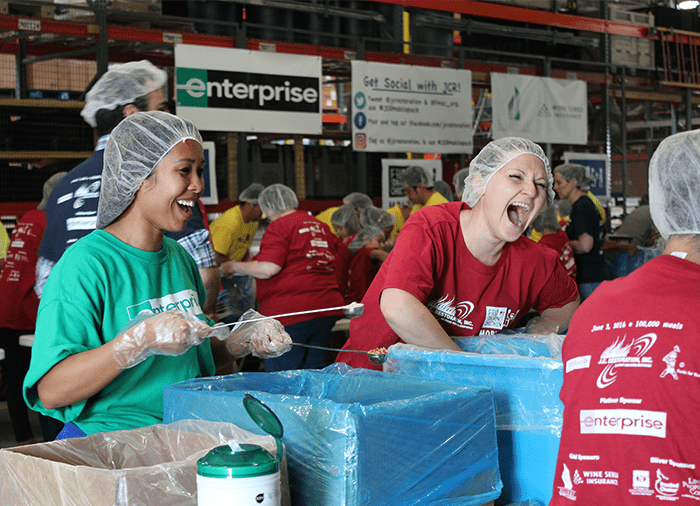 j.c. restoration volunteers packing meals and laughing