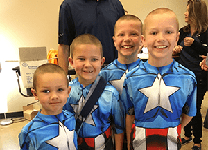 four children volunteers wearing captain america costumes