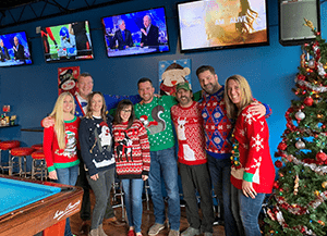 employees wearing ugly christmas sweater