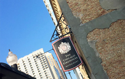The Chicago Firehouse Restaurant Sign hanging on building