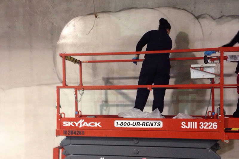 woman fixing drywall in industrial warehouse