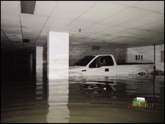 truck floating in parking garage from flood at high rise apartments