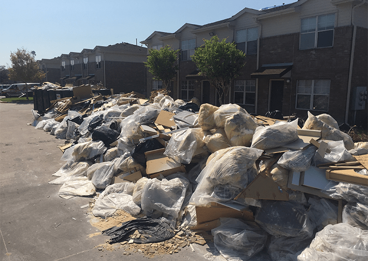 build-up of trash after hurricane harvey outside of apartment buildings