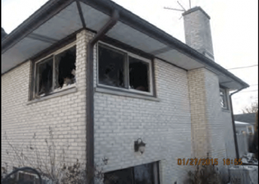 outside view of residential property with broken windows from fire damage