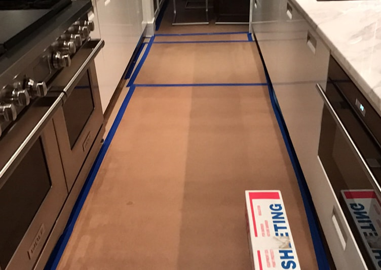 flooring in the kitchen covered and marked up by tape